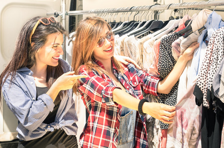 Jonge mooie vrouwen op de wekelijkse doek markt - de beste vrienden te delen vrije tijd plezier en winkelen in de oude stad in een zonnige dag