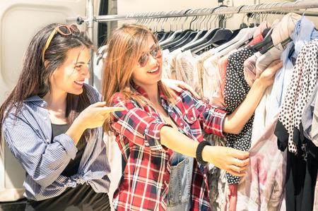 tienda de ropa: Mujeres hermosas jovenes en el mercado semanal de tela - Los mejores amigos que comparten el tiempo libre que tiene diversión y compras en la ciudad vieja en un día soleado