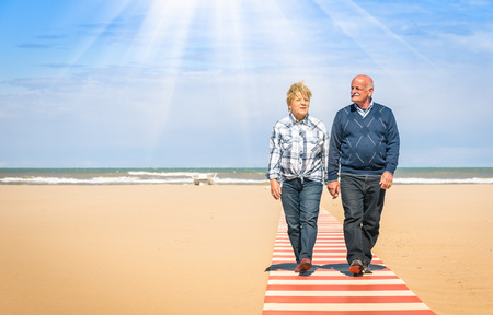 Happy senior couple in love walking hand in hand at the beach - Healthy and joyful elderly lifestyle with man and her wife spending time together outdoors in a sunny day photo