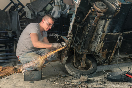Young mechanical worker repairing an old vintage car body in messy garage photo