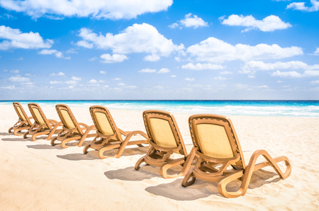 sunbed: Sunbeds chaise longue at tropical empty beach and turquoise sea - Panorama of dream vacation in exclusive destination with white sand in a sunny beautiful day Stock Photo