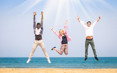 racism: Three multiracial friends jumping at the beach - Concept of happyness and friendship against racism