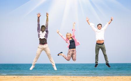 racismo: Tres amigos multirraciales saltando en la playa - concepto de la felicidad y la amistad contra el racismo