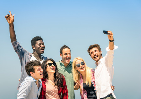 Group of multiracial friends taking a selfie on the blue sky - Concept of happiness and friendship all together against racism