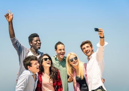 racismo: Grupo de amigos multirraciales tomar una selfie en el cielo azul - concepto de la felicidad y la amistad todos juntos contra el racismo Foto de archivo