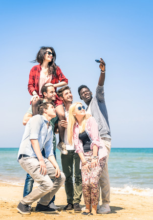 student travel: Group of multiracial happy friends taking a selfie at the beach - Concept of international friendship all together against racism