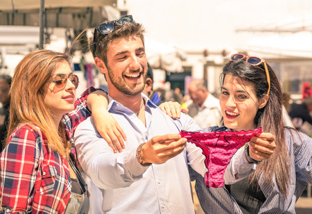 Group of happy young people at the weekly cloth market looking at female underwear - Best friends sharing free time having fun and shopping in the old town in a sunny day photo