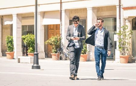 mejores amigas: Los j�venes de negocios en la plaza principal de la ciudad con el tel�fono inteligente con un descanso despu�s de un d�a de trabajo enviando mensajes de texto sms - Concepto moderno de la vida urbana y metropolitana