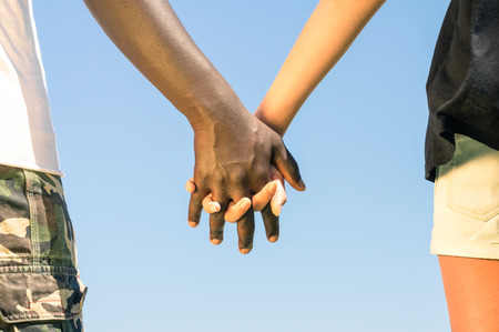 Multiracial couple walking hand in hand against a blue sky - Concept of multi ethnic love over social barriers photo
