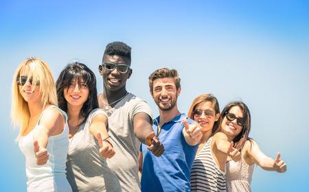 racismo: Grupo de amigos felices multirraciales con los pulgares arriba - Concepto de la amistad y el éxito internacional contra el racismo y las barreras sociales multiétnicas Foto de archivo
