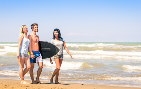 Group of young happy people on vacations at the beach holding a surf table - Best friends with girlfriends having fun in the summer with surfboard boogieboard during travel holidays photo