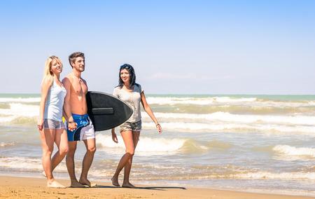 tabla de surf: Grupo de j�venes felices en vacaciones en la playa con una tabla de surf - Los mejores amigos con novias que se divierten en el verano con boogieboard tabla de surf durante las vacaciones de viaje Foto de archivo