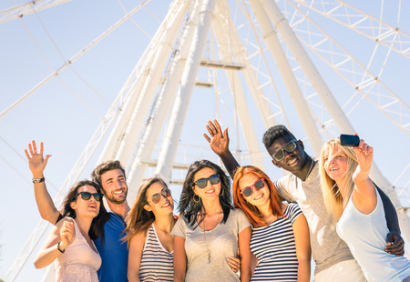 racism: Group of multiracial happy friends taking a selfie at ferris wheel - International concept of happiness and multi ethnic friendship all together against racism for peace and fun