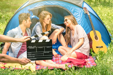 frienship: Group of friends camping in the park - Ciak clapperboard with young actors in the nature - Concept of youth and frienship with vintage scenario