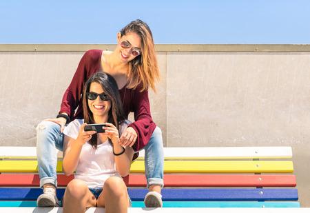 amigos abrazandose: Mejores amigos disfrutando de tiempo juntos al aire libre con el teléfono inteligente - Concepto de la nueva tecnología con dos amigas que se divierten en un banco multicolor