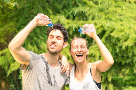 jaded: Sporty couple refreshing with cold water after run training in the park - Sport fitness young happy models taking a break after jogging in the nature