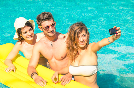 beach mat: Group of best friends taking selfie at the swimming pool with yellow airbed - Concept of friendship in the summer with new trends and technology - Young man with girlfriends enjoying modern smartphone Stock Photo