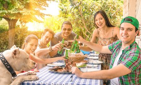 parrillada: Grupo de amigos felices comiendo y brindando por la barbacoa en el jardín - Concepto de felicidad con la gente joven en casa disfrutando de la comida juntos