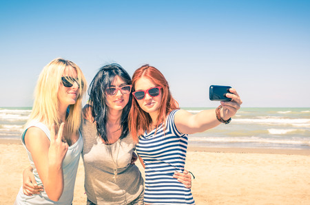 teen bikini: Group of girlfriends taking a selfie at the beach - Concept of friendship and fun in the summer with new trends and technology - Best friends enjoying the moment with modern smartphone