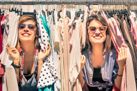 Young beautiful women at the weekly cloth market - Best friends sharing free time having fun and shopping in the old town in a sunny day - Girlfriends enjoying everyday life moments