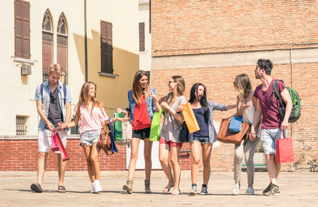 Group of happy best friends with shopping bags in the city center - Tourists walking and having fun in the summer around the old town - University students during a break in a sunny day Фото со стока