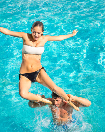Happy young couple in swimming pool jumping from the shoulder - Concept of love and fun with joyful moments in summer - Vacation lifestyle in exclusive hotel resorts