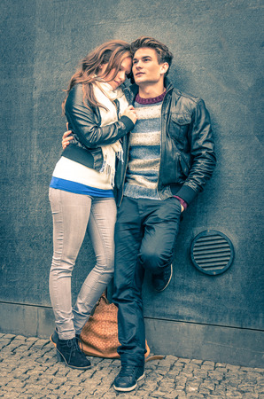 Modern fashion hipster couple of young lovers with autumn clothes ready for the upcoming winter - Deep moment of a love story with a cold vintage filtered look photo