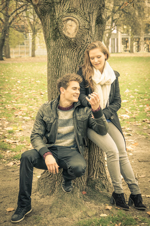 seducing: Modern fashion hipster couple of young lovers with autumn clothes - Deep moment at the beginning of a love story with a nostalgic desaturated filtered look Stock Photo