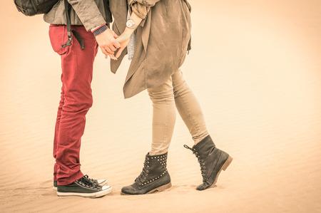 держась за руки: Концепция любви осенью - Пара молодых влюбленных, поцелуи на улице с крупным планом на ногах и обуви - ненасыщенный ностальгию фильтруется взгляд