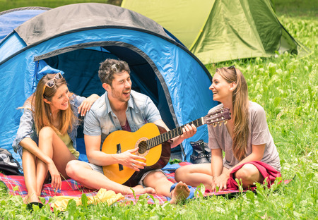 threesome: Group of best friends singing and having fun camping together - Concept of carefree youth and freedom outdoors in the nature - Caucasian young people during vacations
