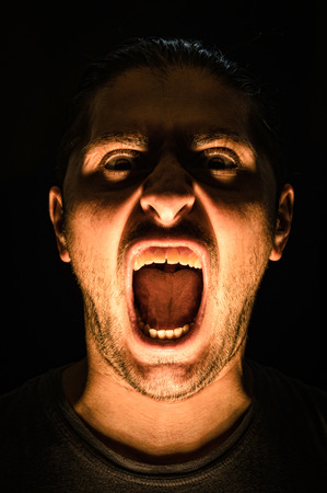 Horror scene with screaming scary human face with a harsh light on a black - Halloween concept with young man with open mouth and teeth photo