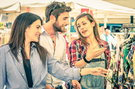 Young tourists at the weekly cloth market - Best friends sharing free time on the weekend having fun and shopping in the old town - Vintage filtered look