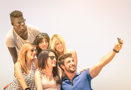 multi racial: Group of multiracial happy friends taking a selfie outdoors - International concept of happiness and multi ethnic friendship all together against racism for peace and fun - Vintage filtered look