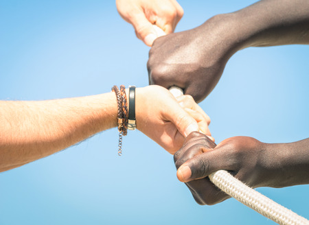tug: Tug of war - Concept of interracial multi ethnic union together against racism - Multiracial hands teamwork