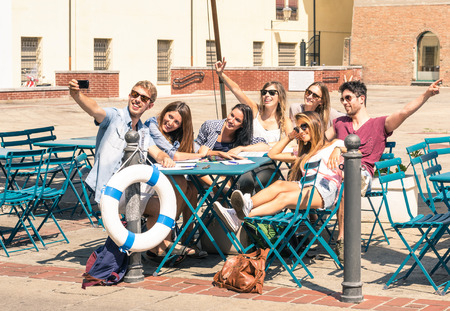 Group of happy best friends taking a selfie - Tourists having fun in the summer around the old town - University students during a break in a sunny day photo