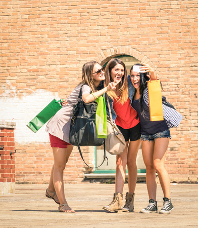 Group of happy best friends with shopping bags taking a selfie in the city center - Girlfriends walking and having fun in the summer around the old town - University students during a break in a sunny day