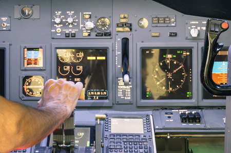 airline pilot: Captain hand accelerating on the throttle in commercial airliner flight simulator - Cockpit thrust levers on the phase of takeoff Stock Photo