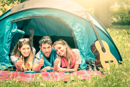 threesome: Group of best friends with thumbs up having fun camping together - Concept of carefree youth and freedom outdoors in the nature during vacations - Vintage filtered look