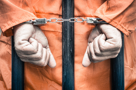 arrested criminal: Handcuffed hands of a prisoner behind the bars of a prison with orange clothes - Crispy desaturated dramatic filtered look Stock Photo