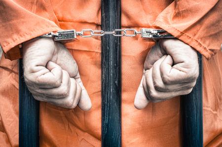 carcel: Las manos esposadas de un prisionero detrás de los barrotes de una prisión con ropa de color naranja - Crispy mirada filtrada dramática desaturado