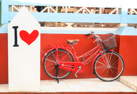 a two wheeled vehicle: Red vintage bicycle with \ I Love \ paint