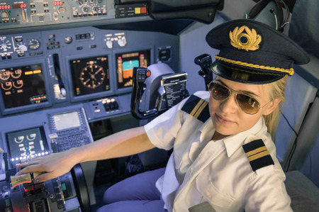 Beautiful blonde woman pilot wearing uniform and hat with golden wings - Modern aircraft cockpit ready for take off - Concept of female emancipation Stock Photo