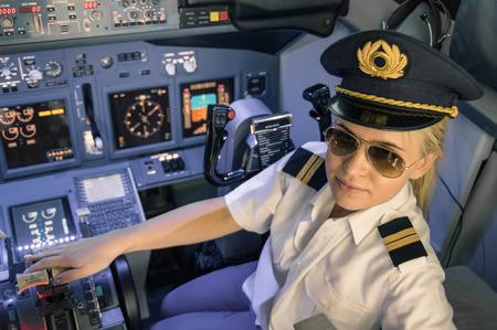 piloto: Hermosa piloto mujer rubia con uniforme y sombrero con alas doradas - cabina de un avión moderno listo para el despegue - Concepto de la emancipación femenina