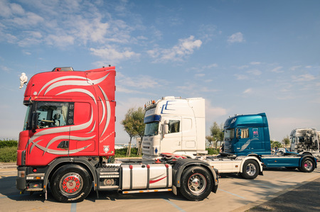 RIMINI, ITALY - SEPTEMBER 7, 2014: Scania semitrucks parked along the beach promenade in Rivazzurra, Adriatic Coast. Scania Aktiebolag is a major Swedish industry manufacturer of commercial vehicles.
