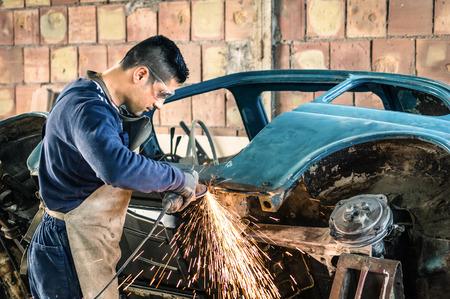 grinder: Joven trabajador mec�nico de reparaci�n de un cuerpo de coches de �poca antigua en el garaje desordenado - Seguridad en el trabajo con el desgaste de protecci�n