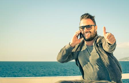 Concept de la technologie en rapport avec le mode de vie de voyageur - Homme modèle montrant le succès d'une entreprise de téléphonie mobile Banque d'images