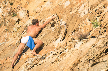 adventurous: Young athletic man free climbing without equipment on dangerous rock slope - Adventurous concept of freedom and contact with wild nature