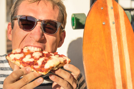 margarita pizza: Young handsome hipster man eating a slice of pizza margherita - Youngster vintage lifestyle during longboard action and take away food