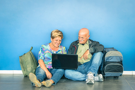 gente aeropuerto: Feliz altos joven sentado en el piso con ordenador portátil de espera para un vuelo en el aeropuerto - Concepto de ancianos activos y la interacción con las nuevas tecnologías - el estilo de vida de viajes sin límite de edad