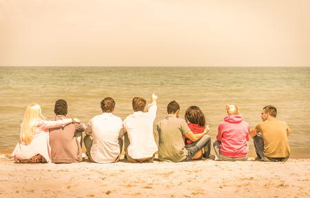 互いに話していると海 - 人種差別と多文化的な友情の概念 - の温かいビンテージ フィルター見て考えているビーチに座って国際多民族の友人のグル